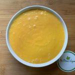 En esta imagen aparece un bol de queso vegano para dipear o queso cheddar vegano.