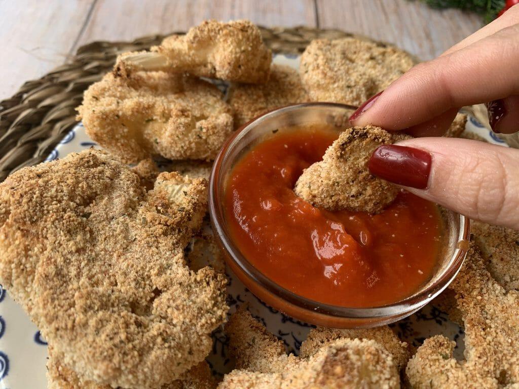 En esta imagen aparece una mano mojando un nugget en la salsa de tomate